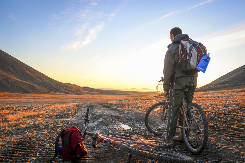 Man standing on a bike looking at the sunset over the mountains in the tundra in canada's high arctic in alert nunavut